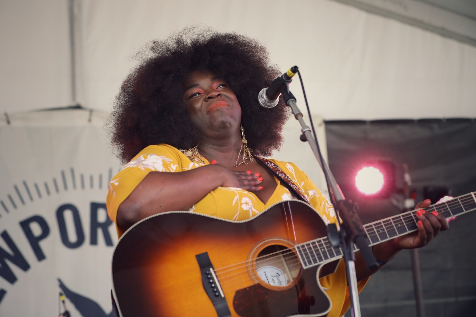 Yola, wearing a yellow dress, places her hand over her heart while holding a guitar at Newport Folk Fest.