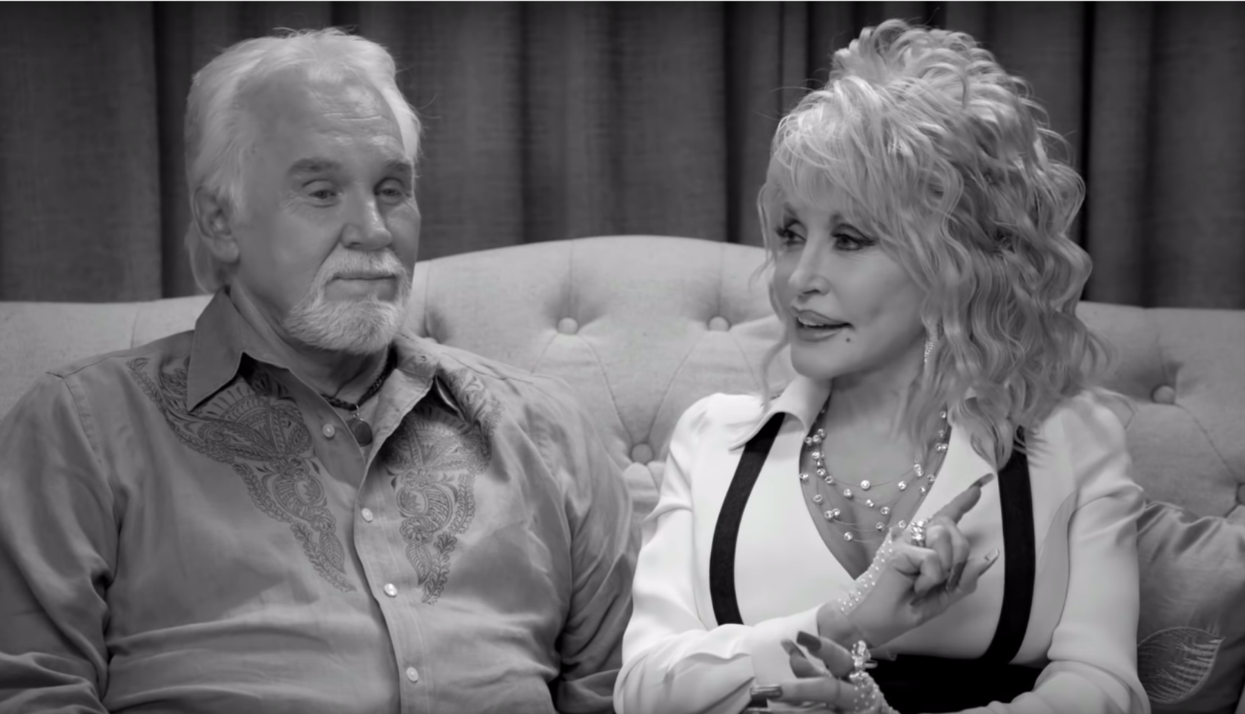 Kenny Rogers and Dolly Parton in black and white seated on a couch
