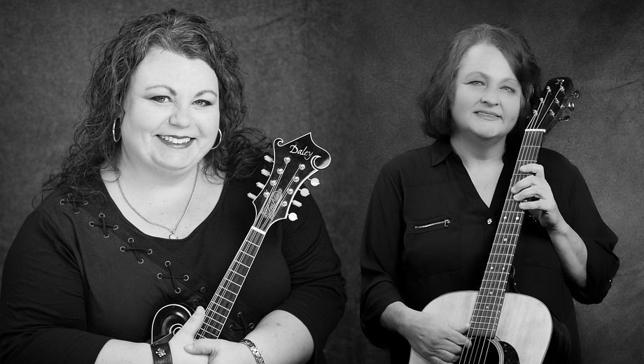A black and white photo Tina Adair (left) holding a mandolin and Dale Ann Bradley (right) holding a guitar.
