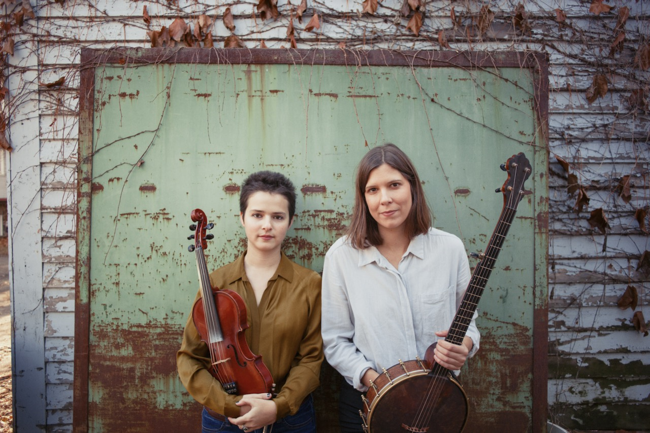 Tatiana Hargreaves with a fiddle and Allison de Groot with a banjo in front of a rustic, worn down wall covered in vines.