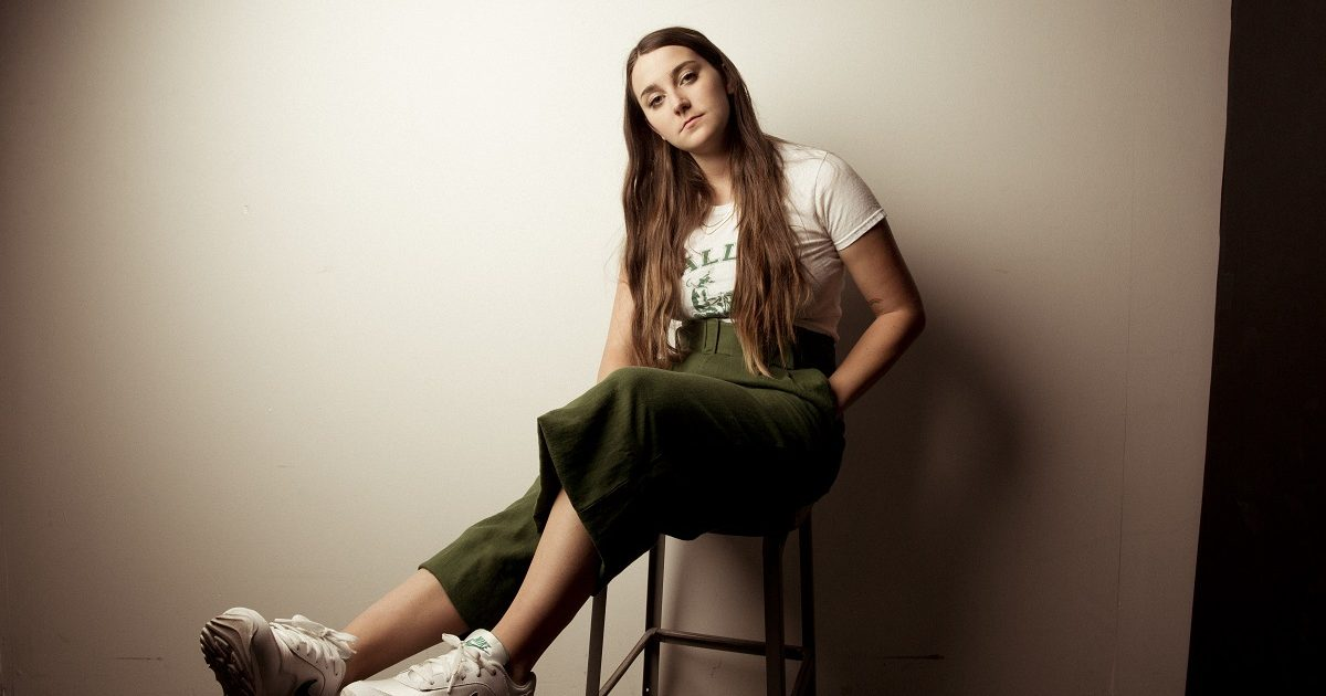 Katie Pruitt sits on a stool, leaning against a wall with tennis shoes on.