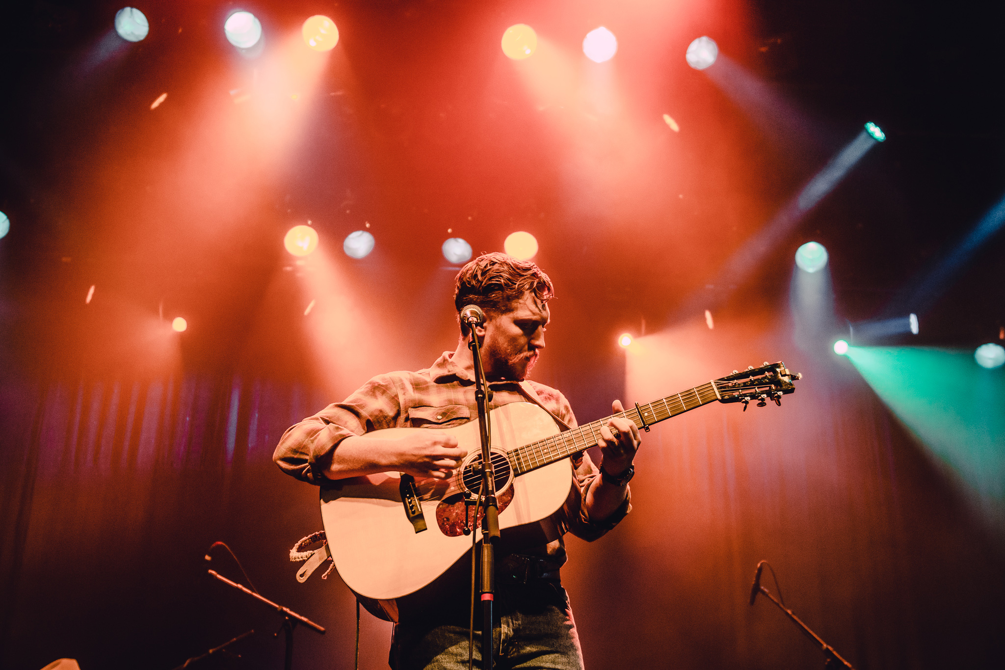 Tyler Childers playing guitar on stage with dramatic stage lights.