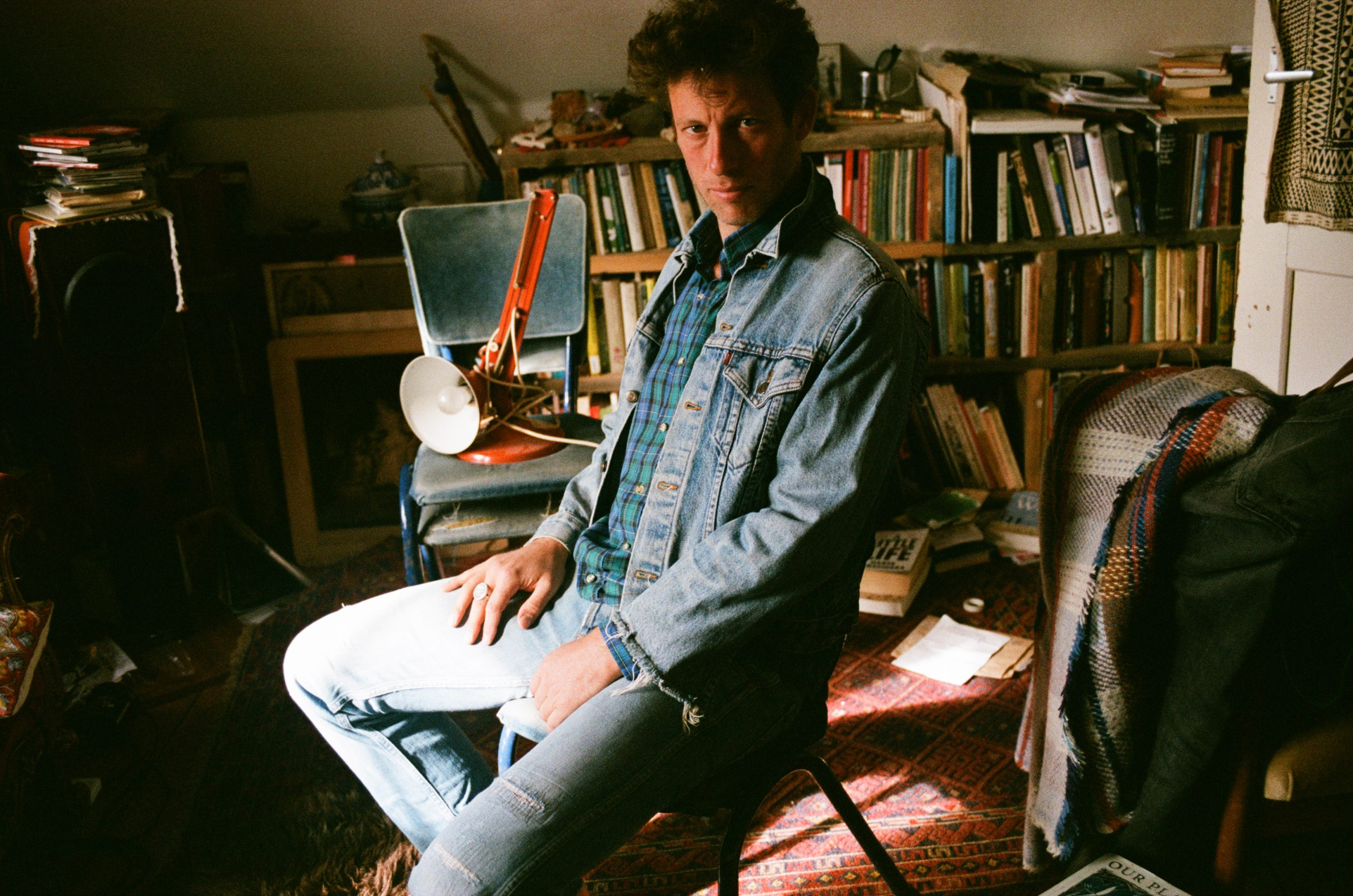 Sam Lee, wearing denim, sits in a cluttered room in front of a bookshelf