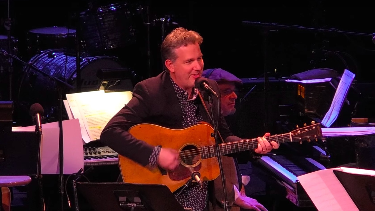 Bryan Sutton holding his guitar on stage at Live From Here with Chris Thile