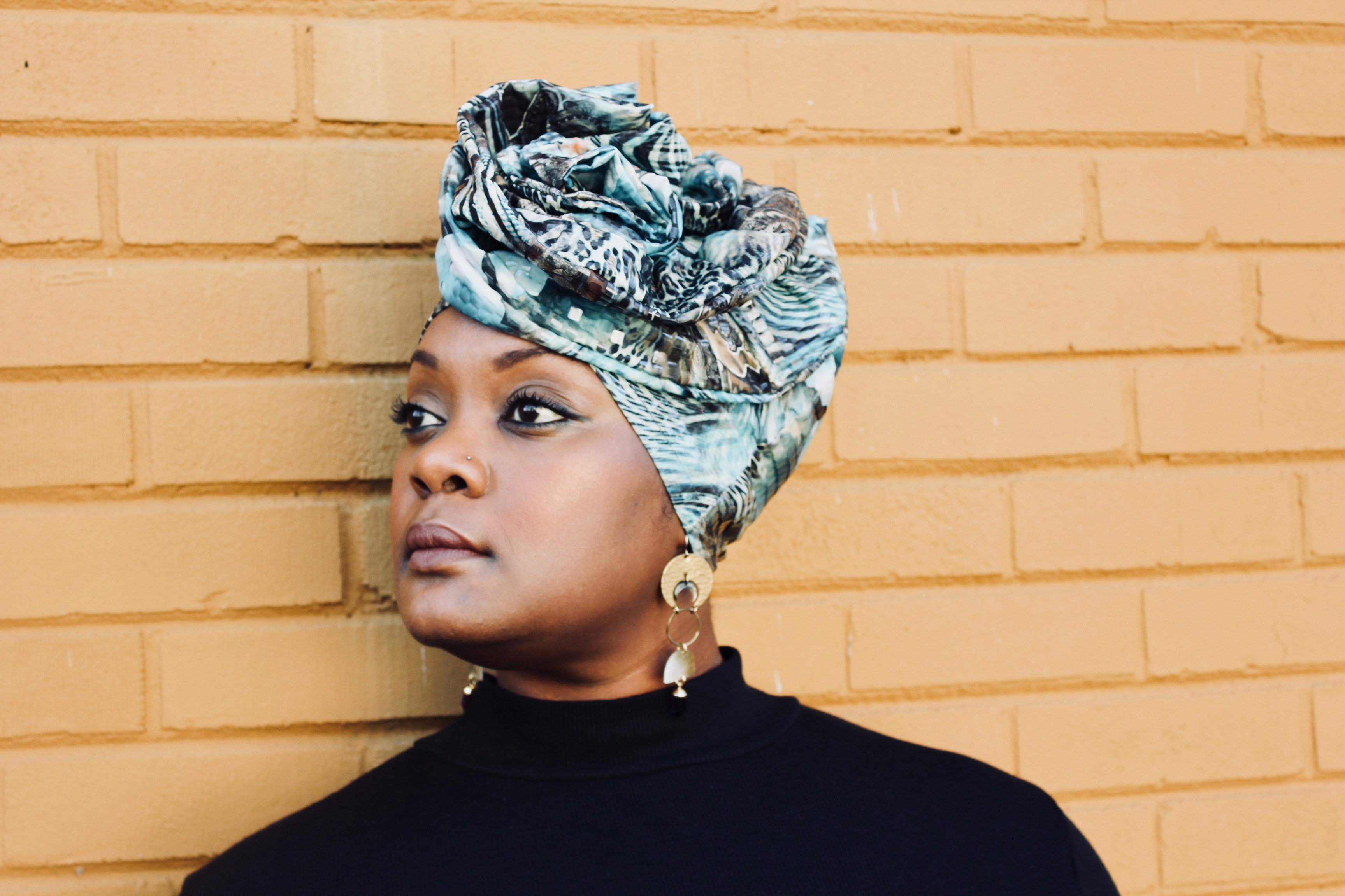 Kyshona with a colorful headscarf standing in front of brick