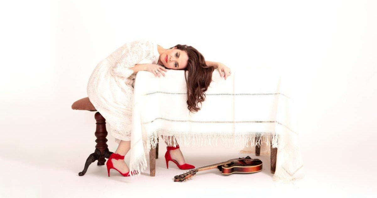 Sierra Hull wears white, sitting at and resting her head on a white table, with her mandolin beneath it.