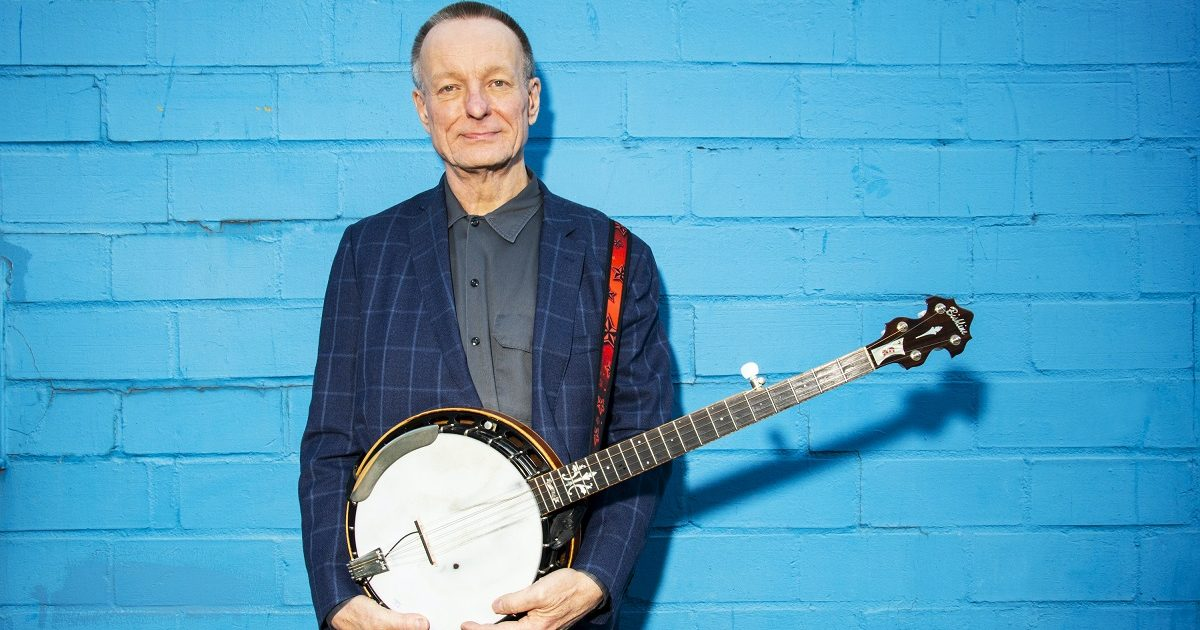 danny barnes standing in front of a blue wall with a banjo